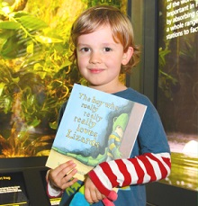 Boy holding 'The Boy who really, really, really, loves Lizards' book at the Vivarium at Manchester Museum