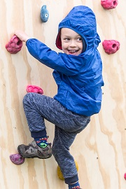 Child enjoys climbing wall at the Geronimo Festival