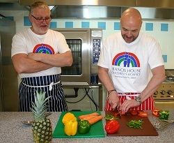 Simon Rimmer demonstrates vegetable preparation skills to Dean Jenkins, chef of Francis House.