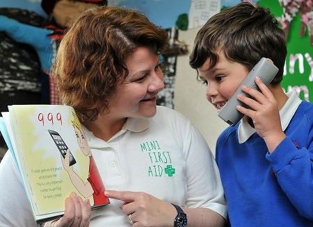 King's Junior and Infant Division pupil learns emergency phone numbers with the help from Mini First Aid representative