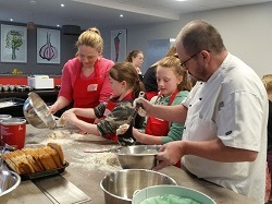 Jayne cooking with her kids at Food Sorcery Big and Little Cook Event