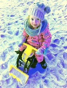 Girl on a rid-on digger playing in the snow